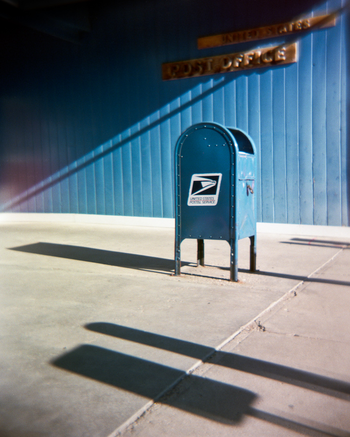Photo of a mailbox in front of a U.S. Post Office building.