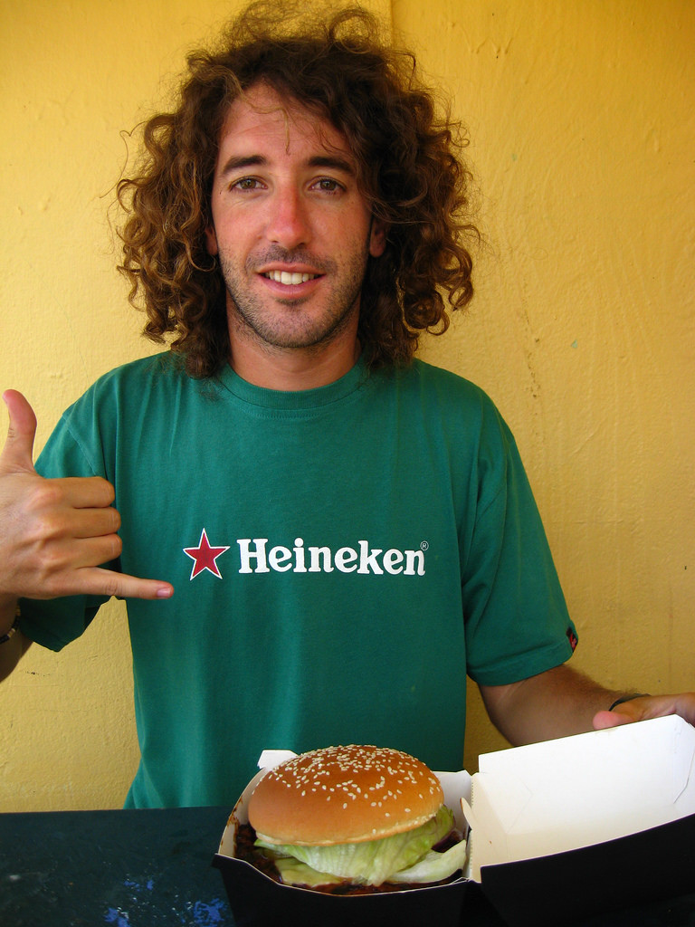Photo of a young man enthusiastically pointing to a hamburger in a takeout box.