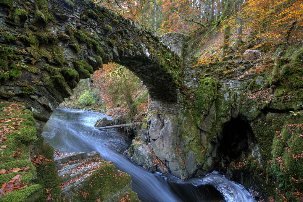 Photo of a rushing mountain stream beneath and old arched stone bridge. Mossy banks, brilliant orange leaves on the trees and ground.