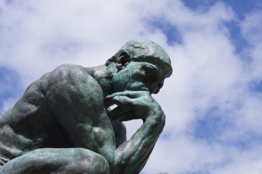Photo of Rodin's statue The Thinker: a bronze man in a crouched position, with his chin resting in his hand.