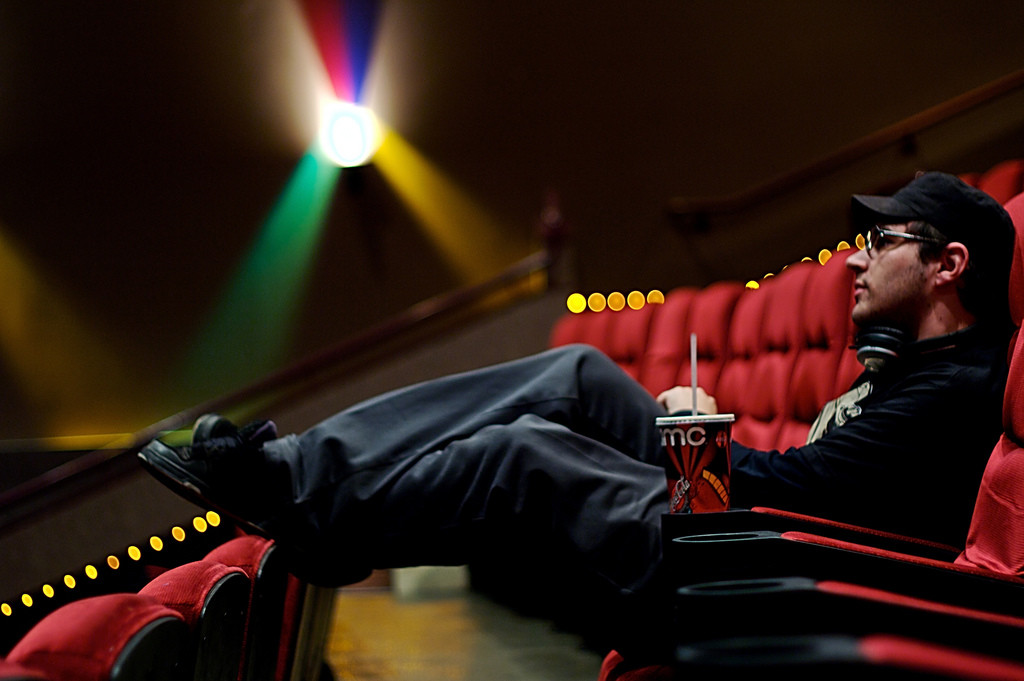 Photo of a man wearing sunglasses, sitting in an empty movie theater holding a soda.