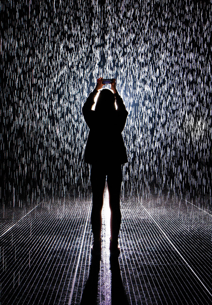 Photo of a woman in silhouette staring upward in the MoMA rain room.