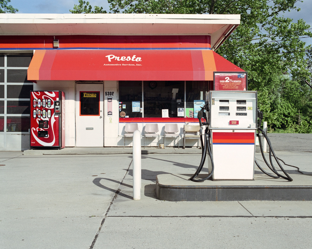 Photo of a small red and white gas station and gas pump.