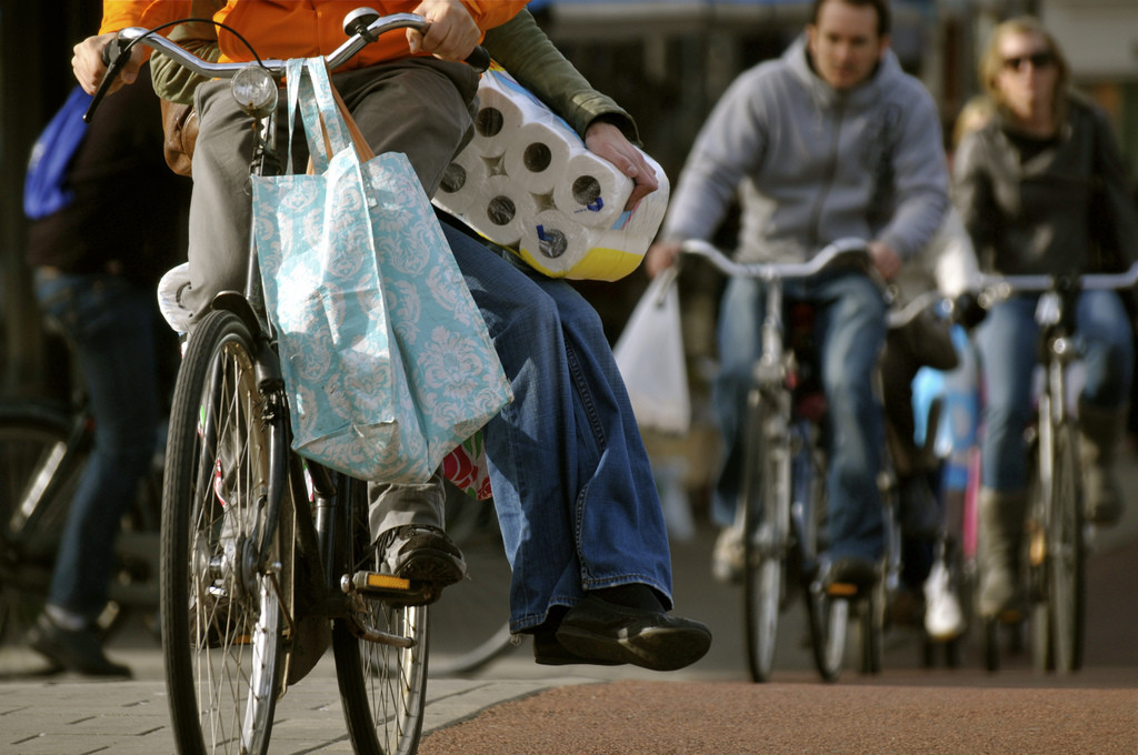 Photo of the lower half of a couple riding a bike. The person in the back sits sidesaddle and is carrying a large package of toilet paper.