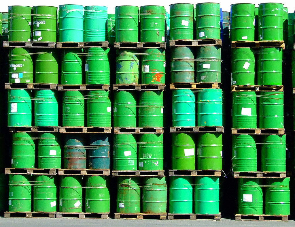 Five stacked rows of green-colored oil barrels.