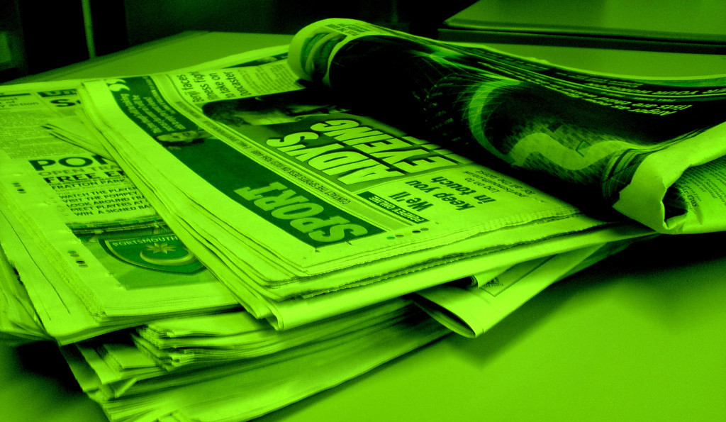 Photo of four folded newspapers; photo is very green
