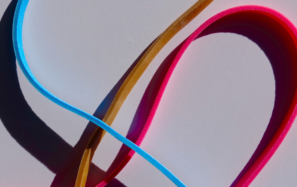 Close-up of three brightly colored rubber bands (blue, gold, and red).