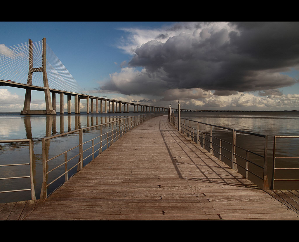 Photo of a long wooden boardwalk that extends toward the horizon and disappears. In the background on the left is a graceful suspension bridge.