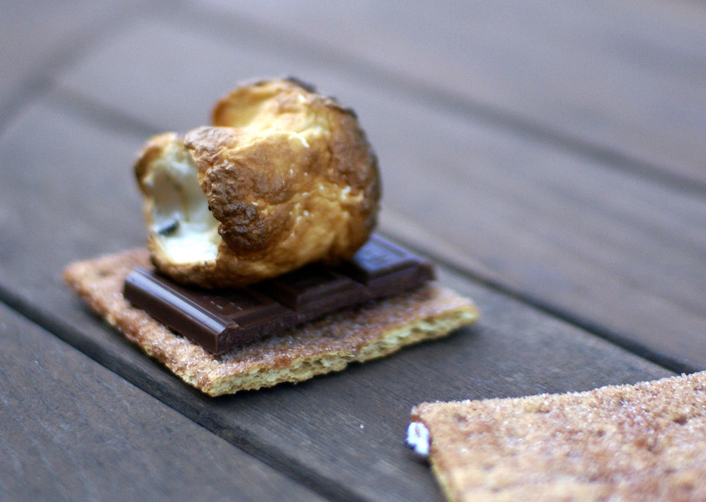 Photo of a s'more: perfectly toasted marshmallow atop a square of chocolate on a graham cracker.