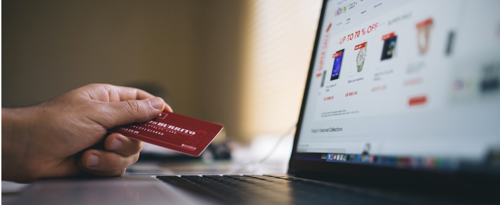 A photograph shows a person sitting at a laptop that is open to e bay. He is holding a member's loyalty credit card in his hand.