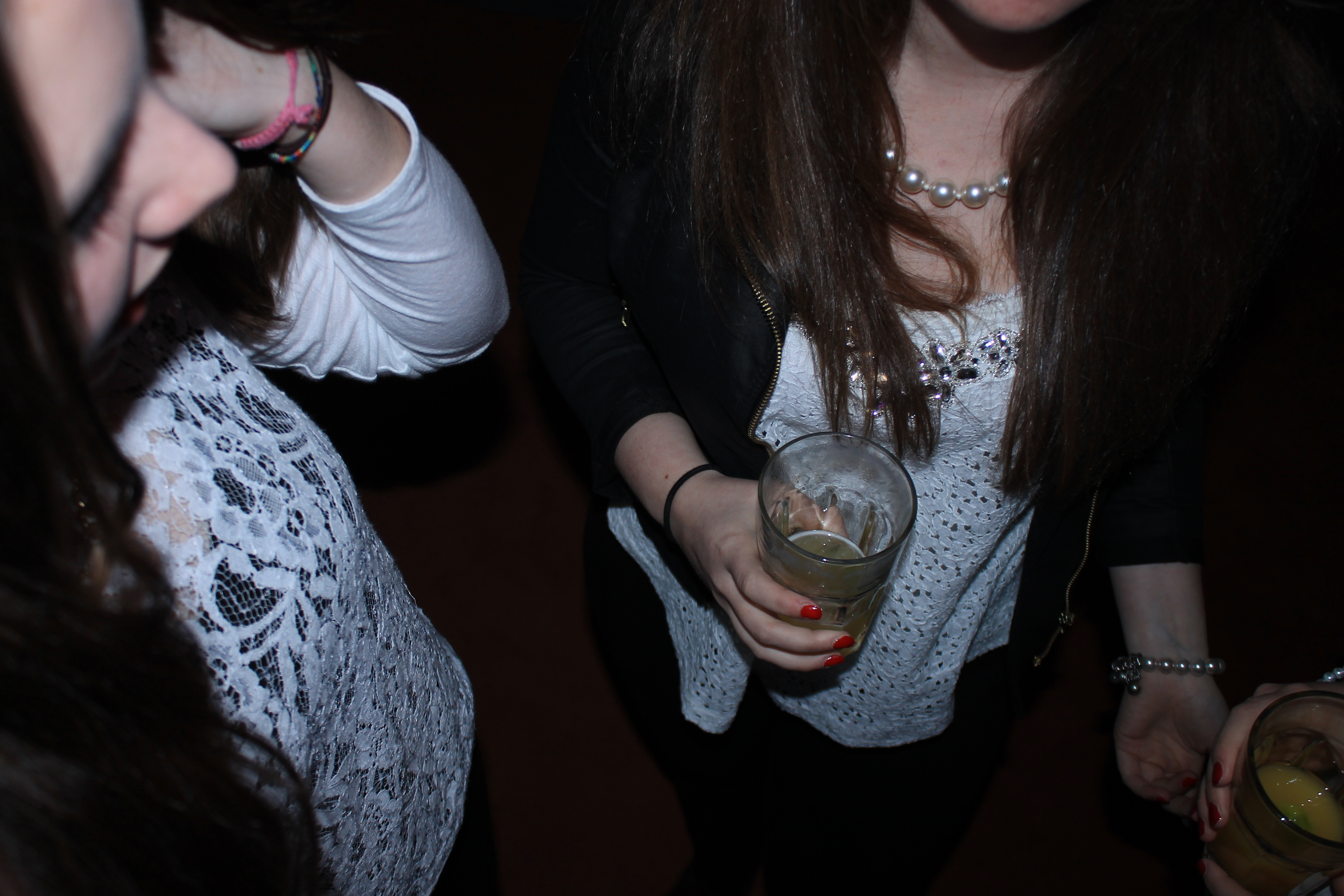 Teen girls holding drinks at a party.