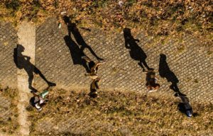 Several people walking down a street shown from above