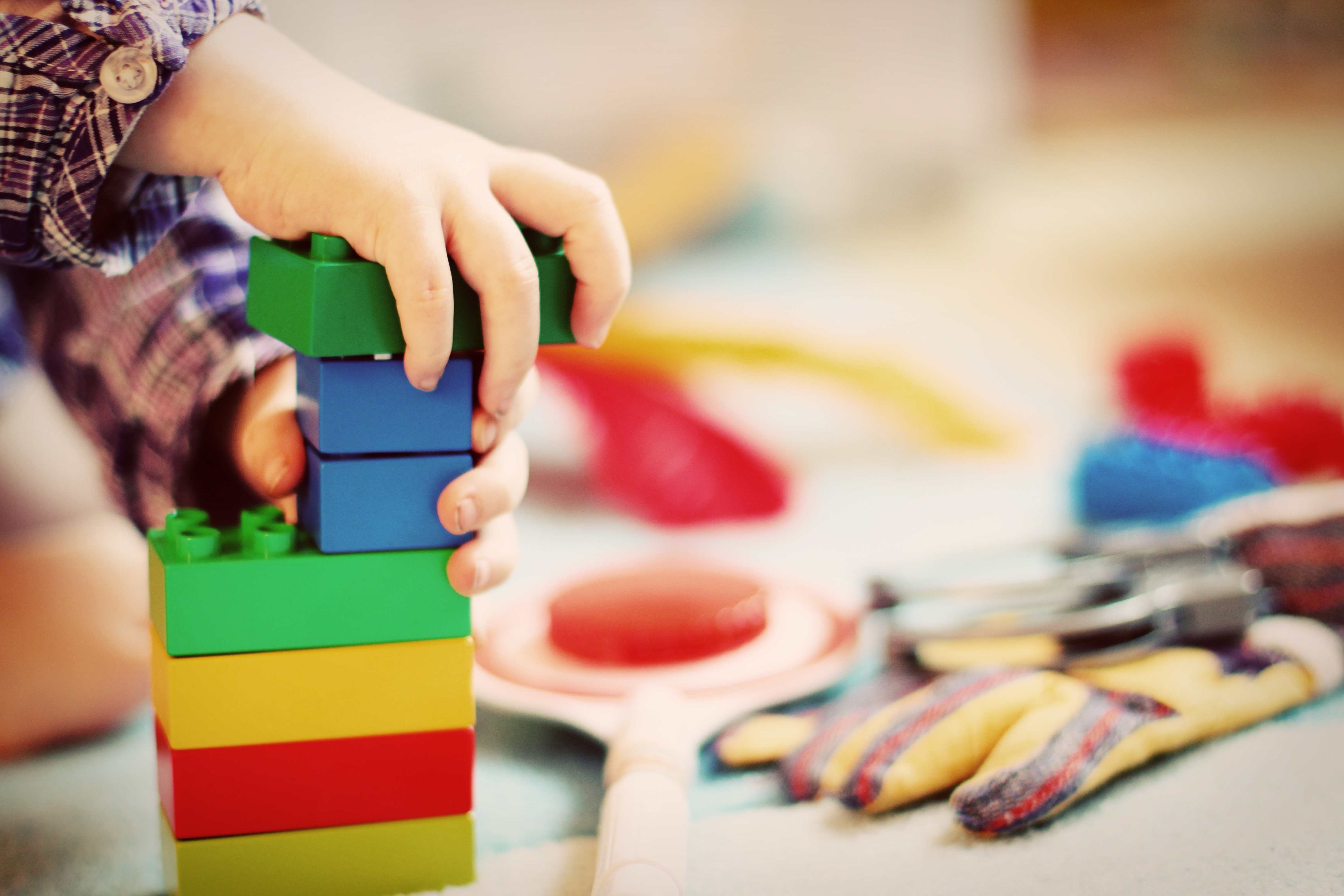 A toddler building a tower out of colorful blocks