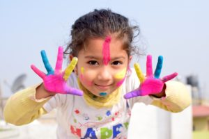 A girl with outstretched hands painted with different bright colors