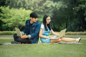 2 people sitting together on the grass looking at their laptops