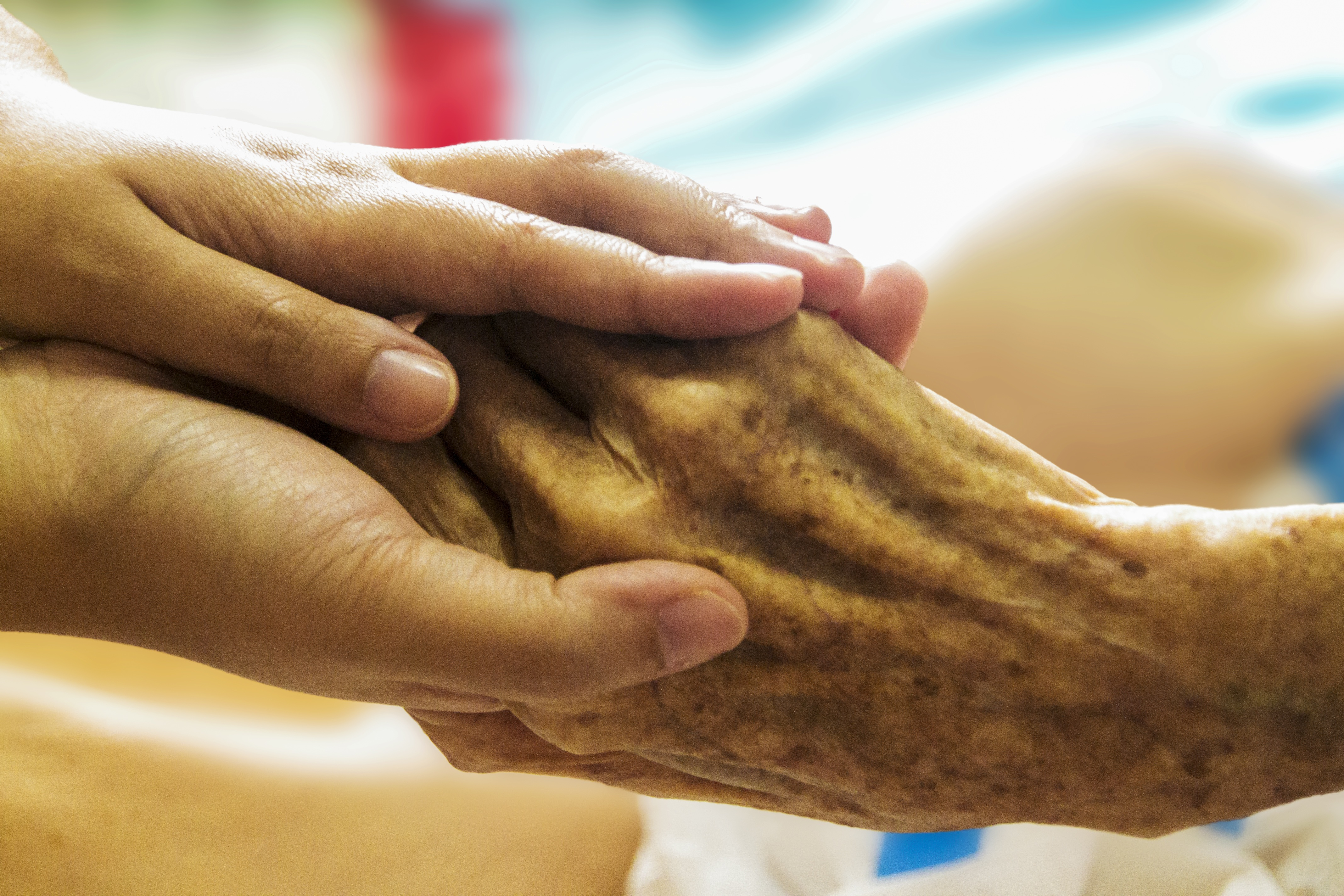 younger hands holding an aged hand.