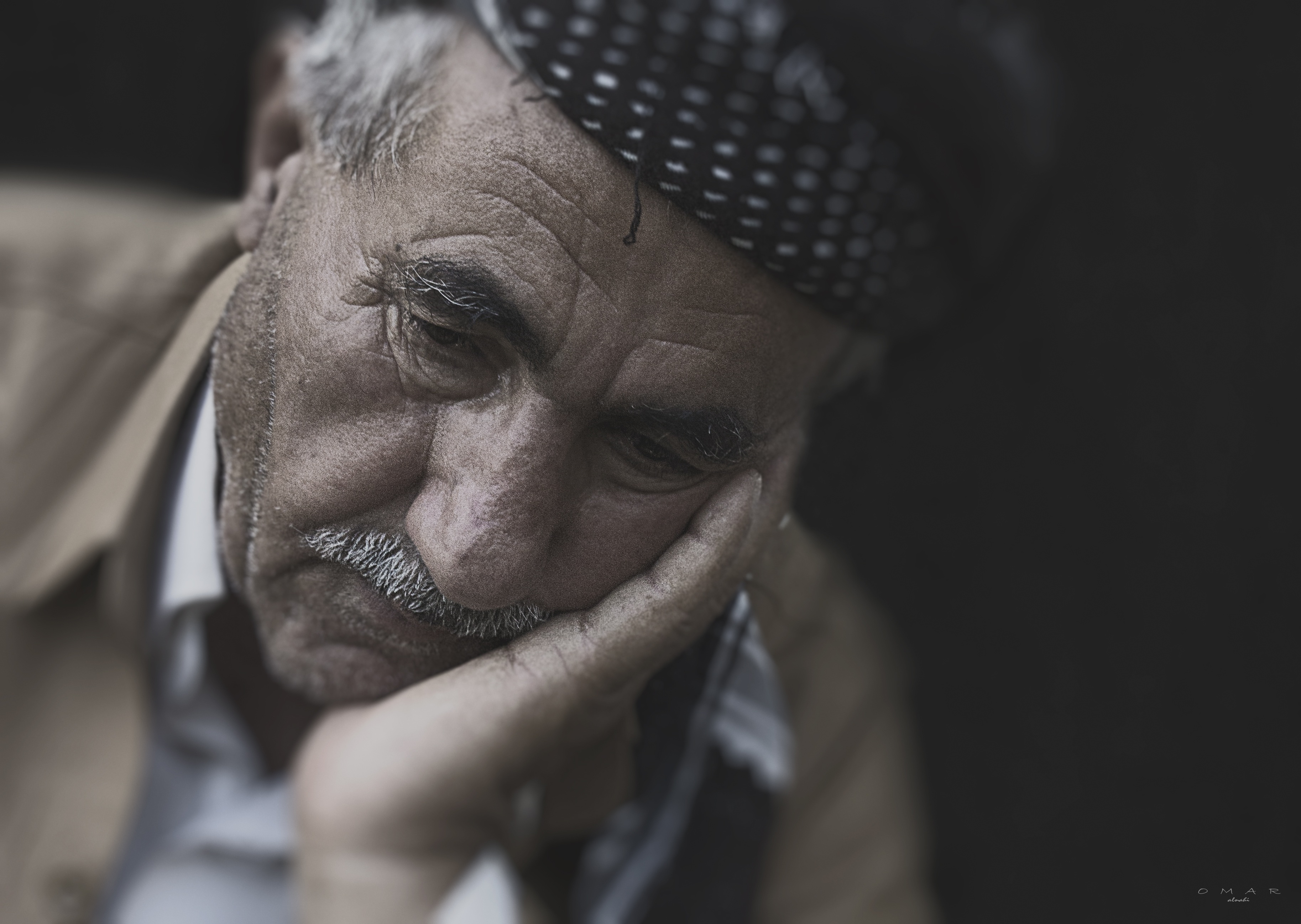 Elderly man resting his head in his hand, looking forlorn.