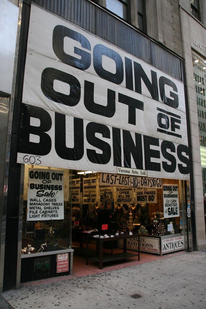 "A store front with a large sign in black and white that says ""going out of business""."