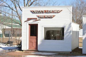 "A storefront called ""Louie's Leather Shoe Repair"". The building is white with a brown door. There is another building in the background and some trees. The trees are bare and there is snow on the ground."