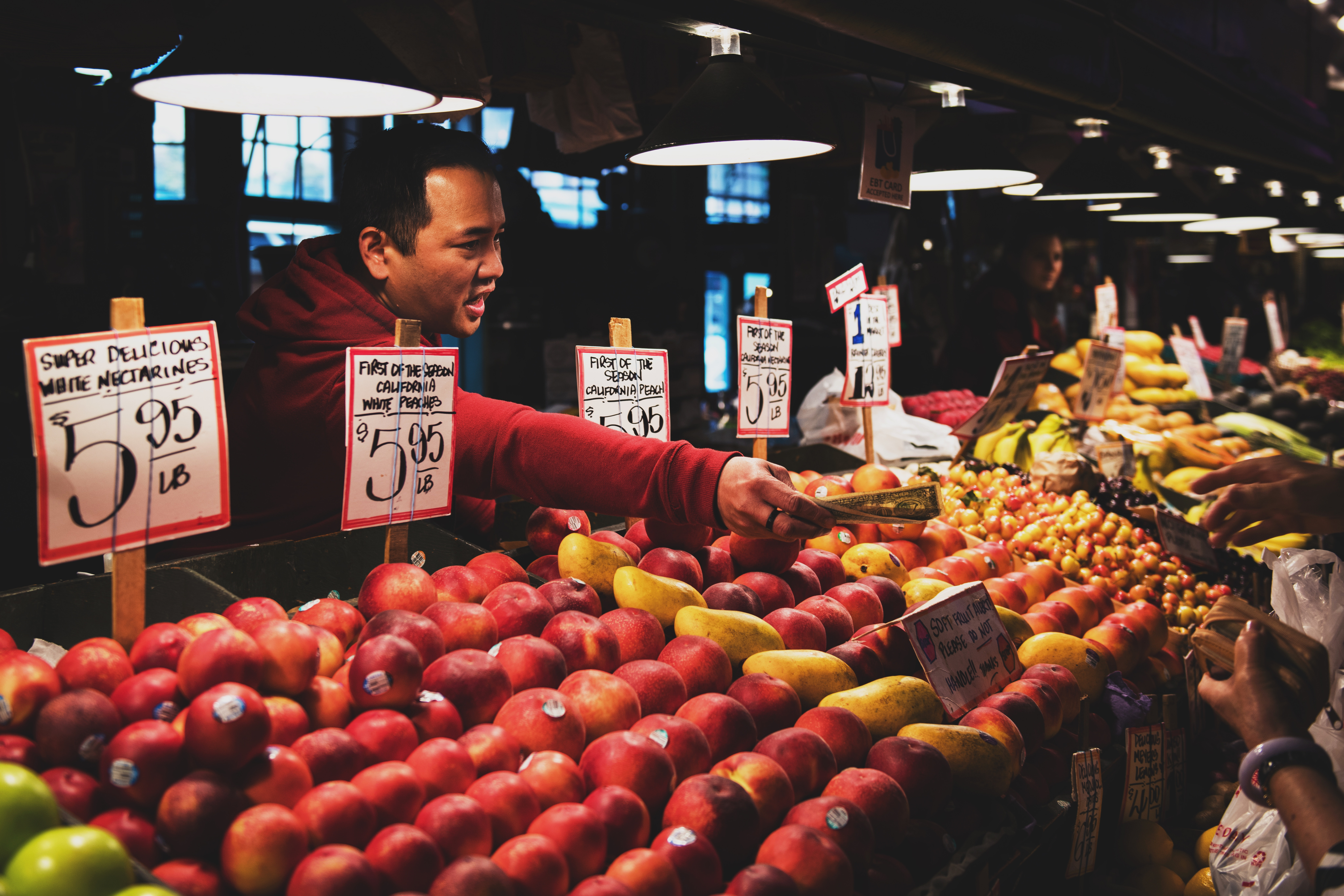 cashier giving a customer change at fruit stand