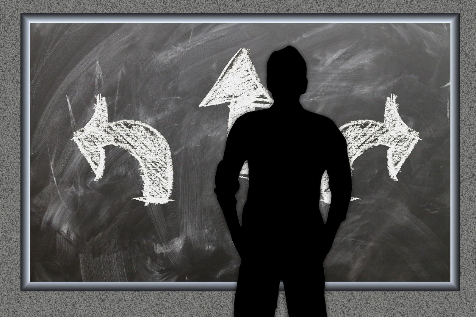 Image of a silhouetted figure standing in front if chalkboard with drawing of three arrows pointing out.