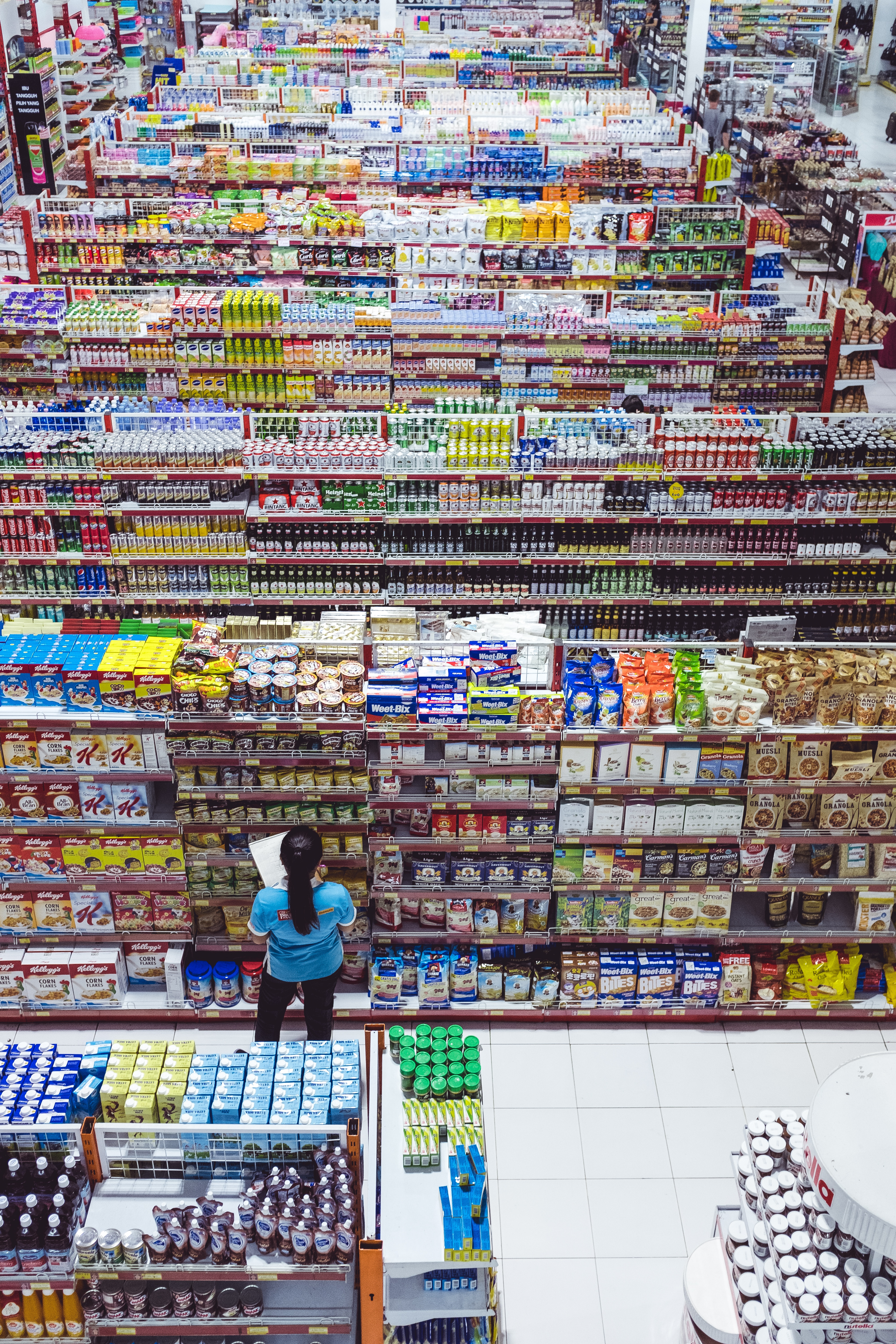 Photograph of an employee checking inventory levels on the shelves at a grocery store.
