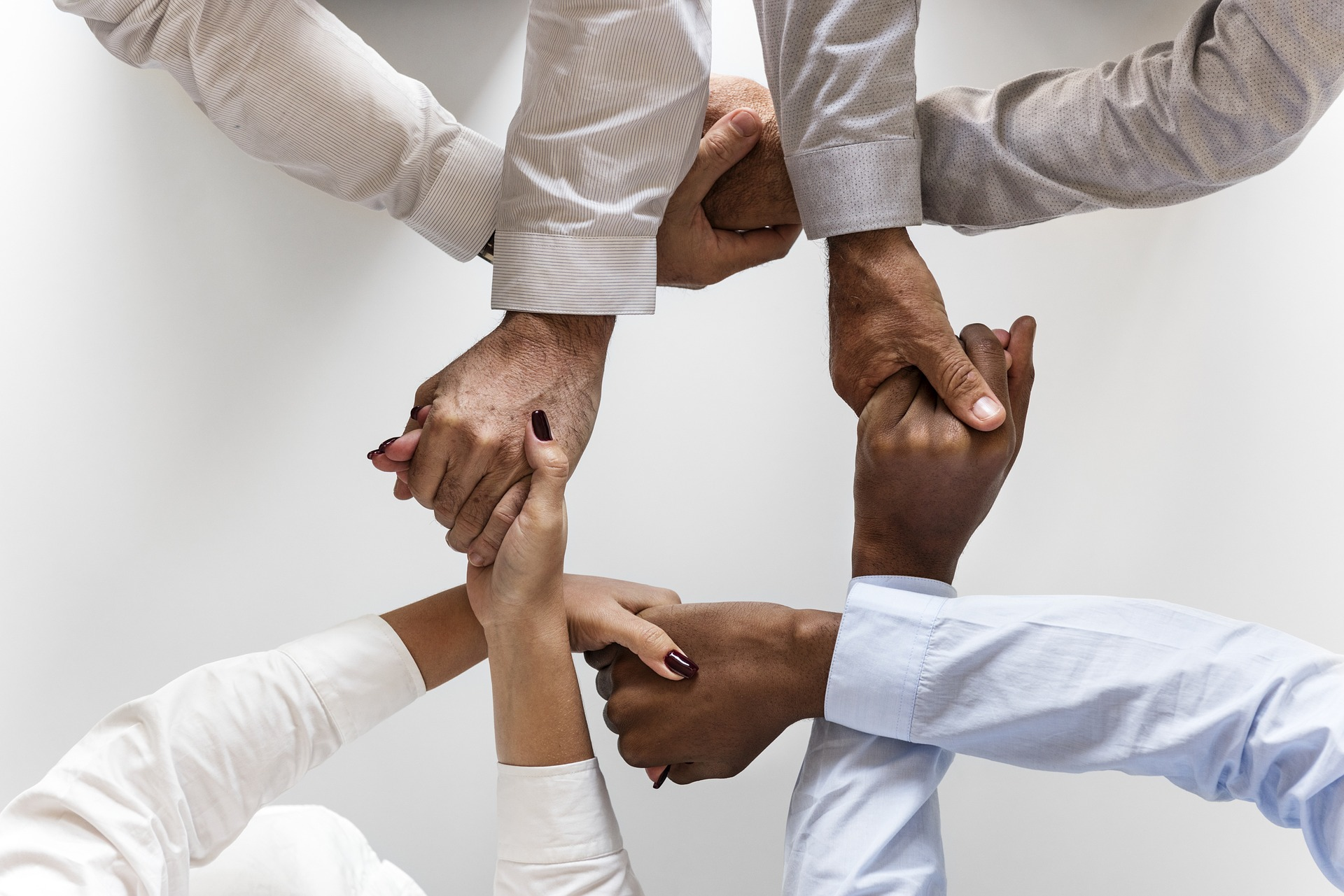 four people holding hands in a circle.