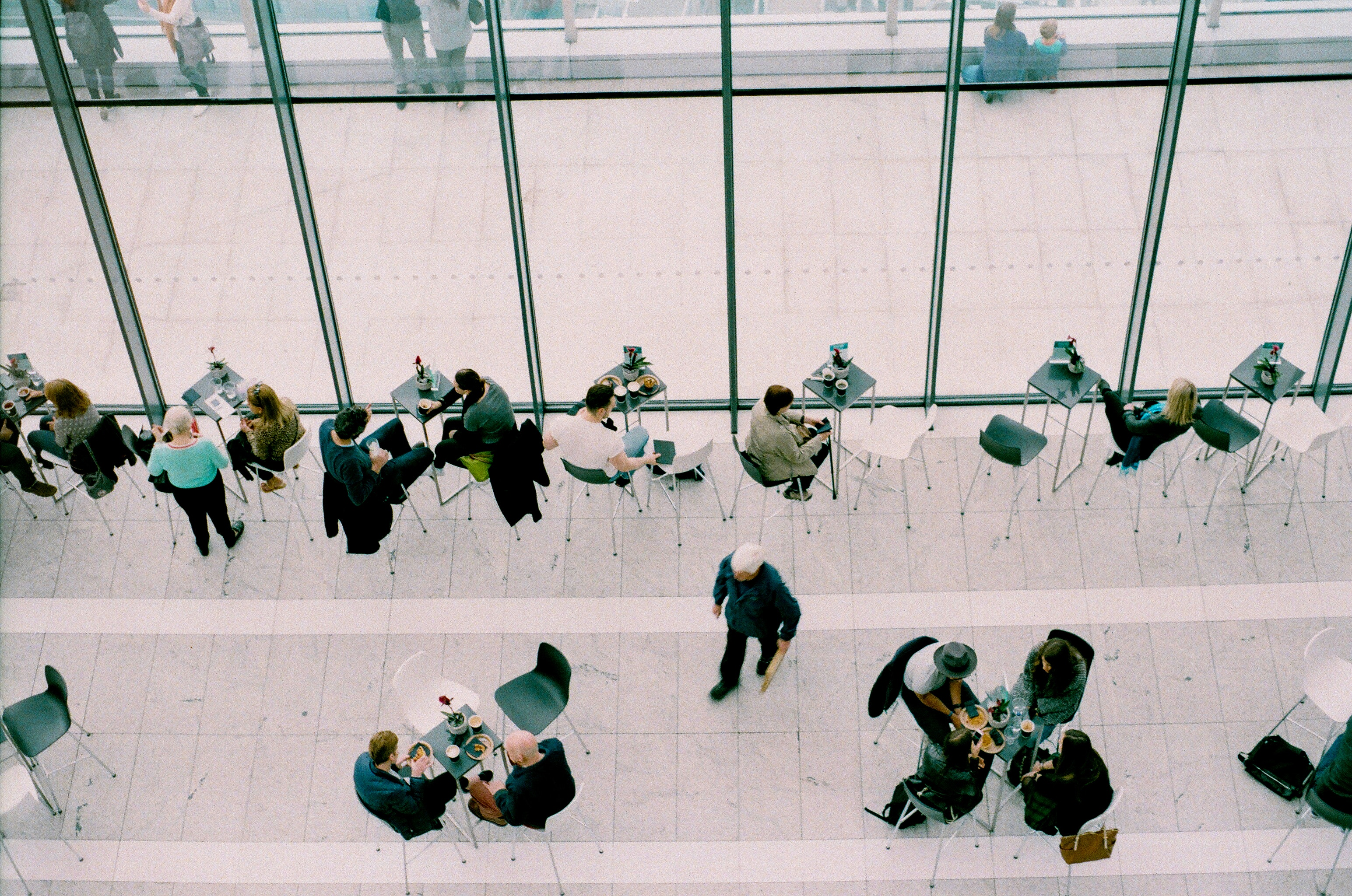 Aerial photo of several small groups of people sitting at tables in a professional work space
