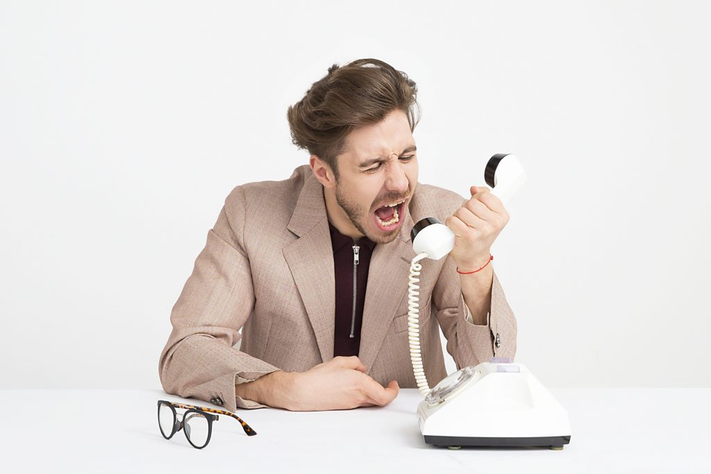 Photograph of a man yelling into a phone