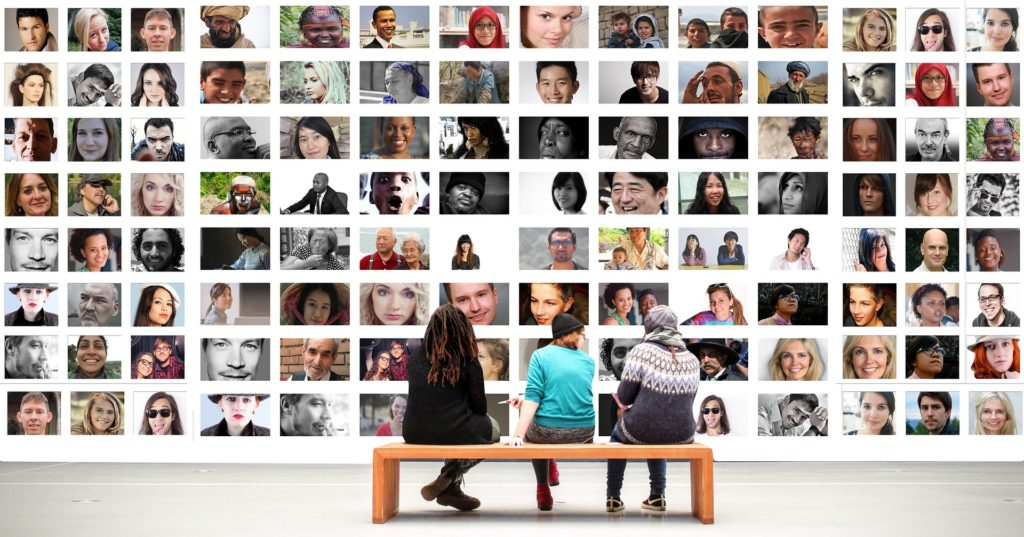 Three people sitting on a bench facing a wall. On the wall are several pictures of individuals of diverse ages, races, genders, and cultures.