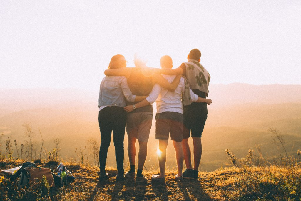 A photo of four people facing away from the camera looking at the sunset. The people have their arms over one another's shoulders.