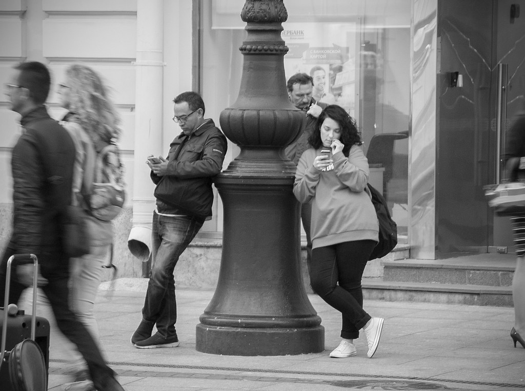 Photograph of two people leaning on a pillar in a busy street while others walk by. Both people leaning on the pillar are using their smart phones.