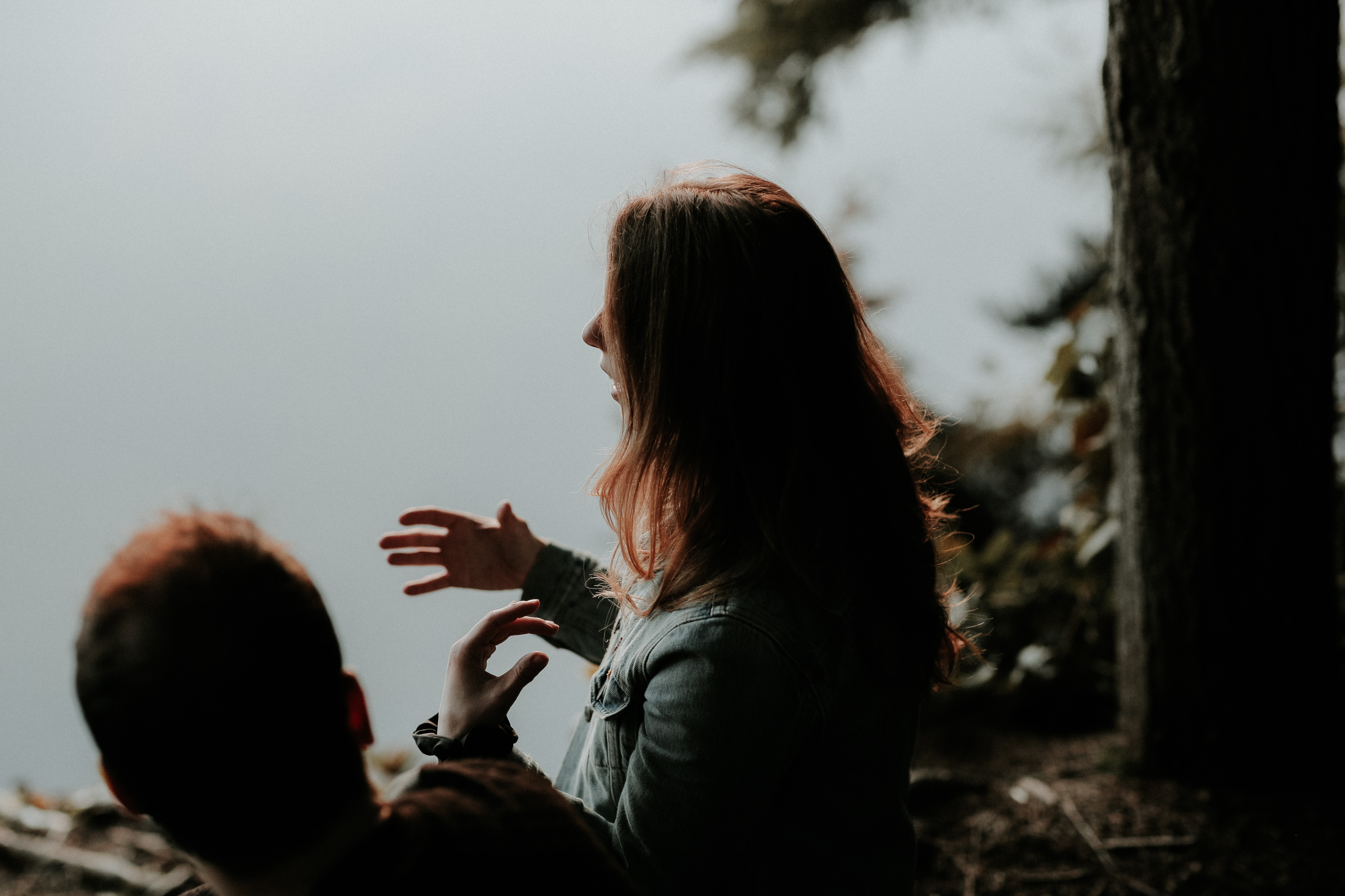 Photograph of a woman sitting next to a man. She is gesturing with her hands as she speaks.