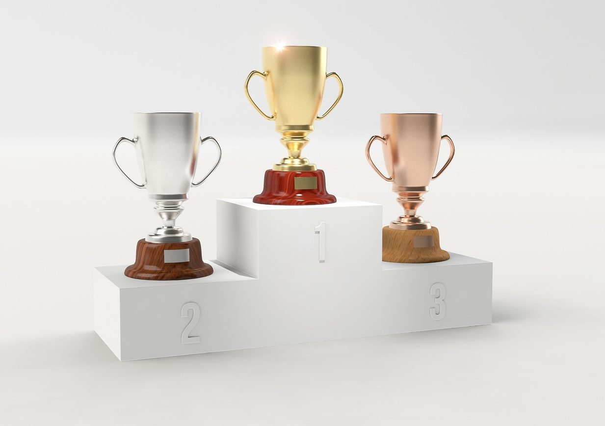 Image of gold, silver, and copper trophies set on risers indicating first, second, and third place.