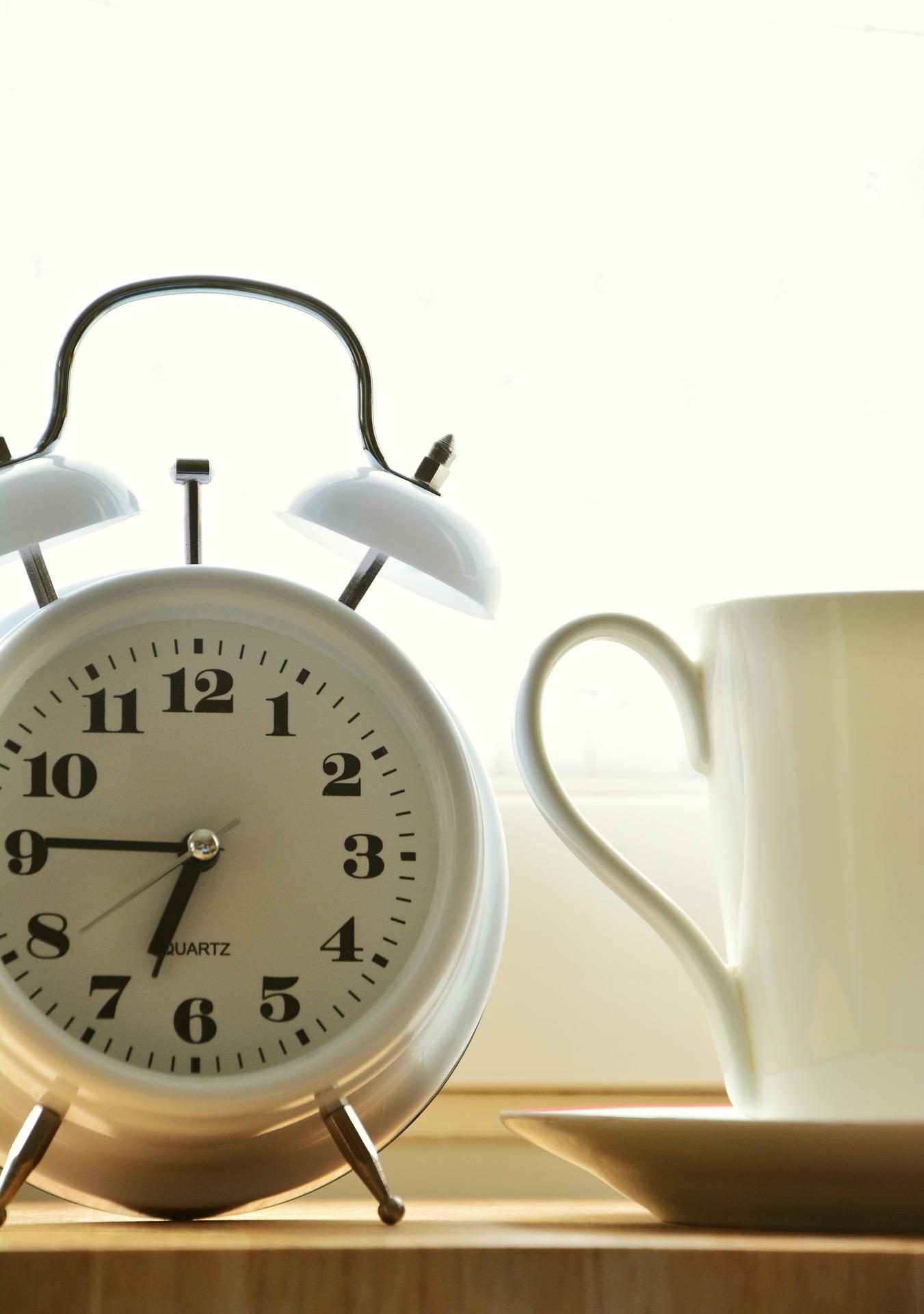 an alarm clock next to a mug.