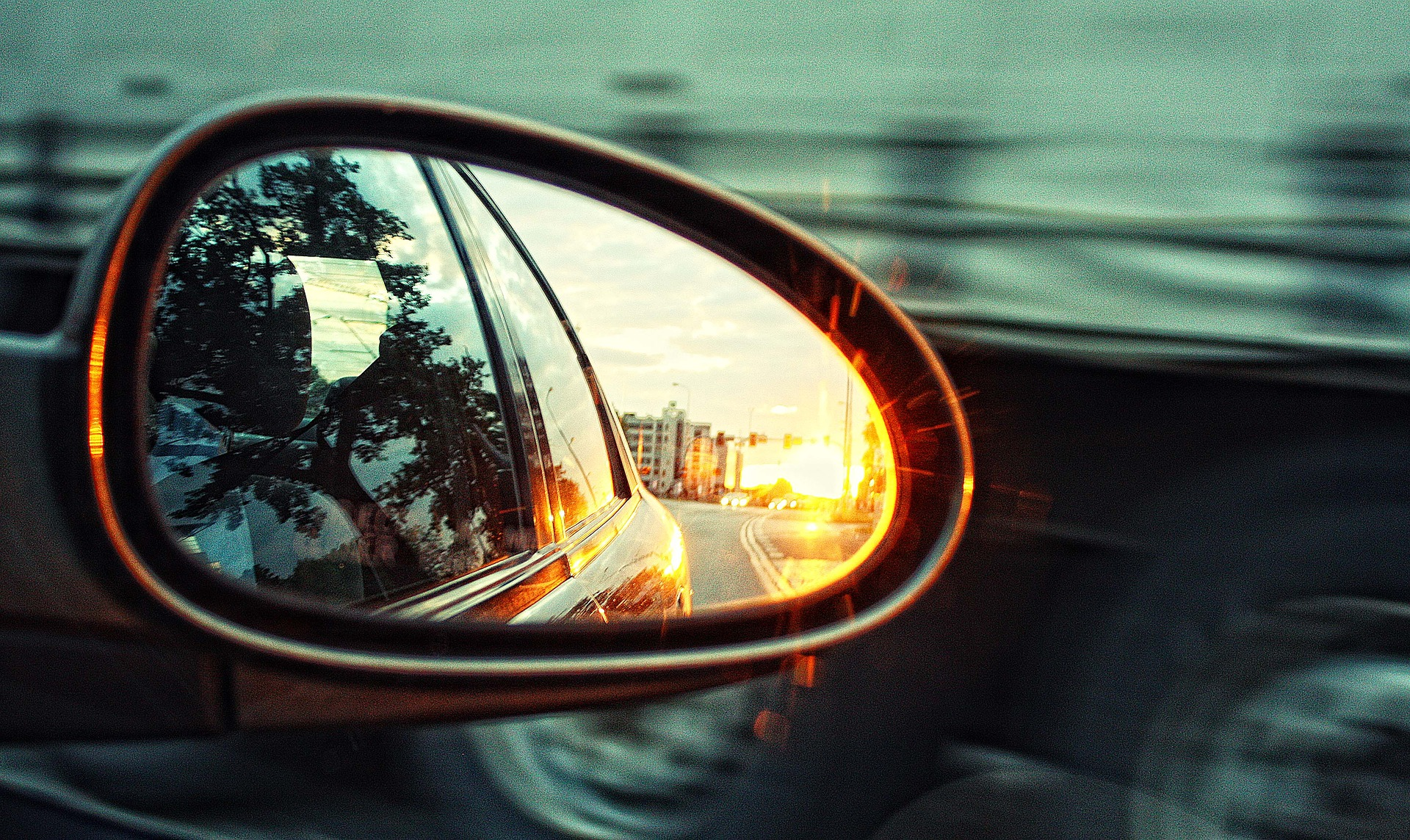 Photo of a car's side mirror, showing the road and a city behind the car