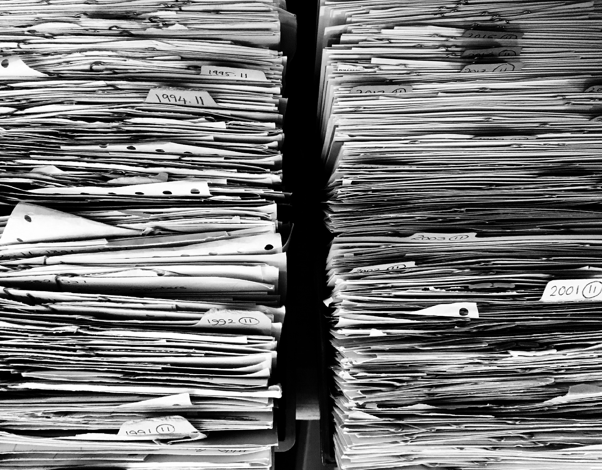Stacks of papers with makers separating annual segments from the year 1991 to 2012.