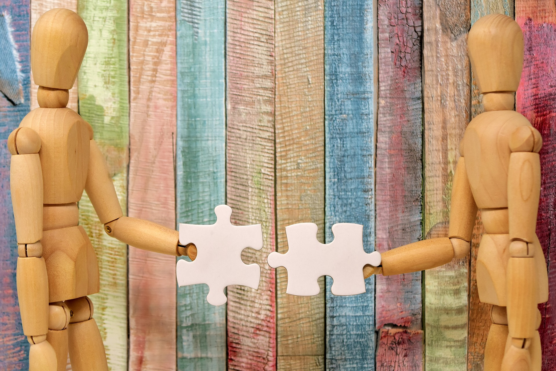 Image of two wood mannequins. Each is offering a puzzle piece to the other.