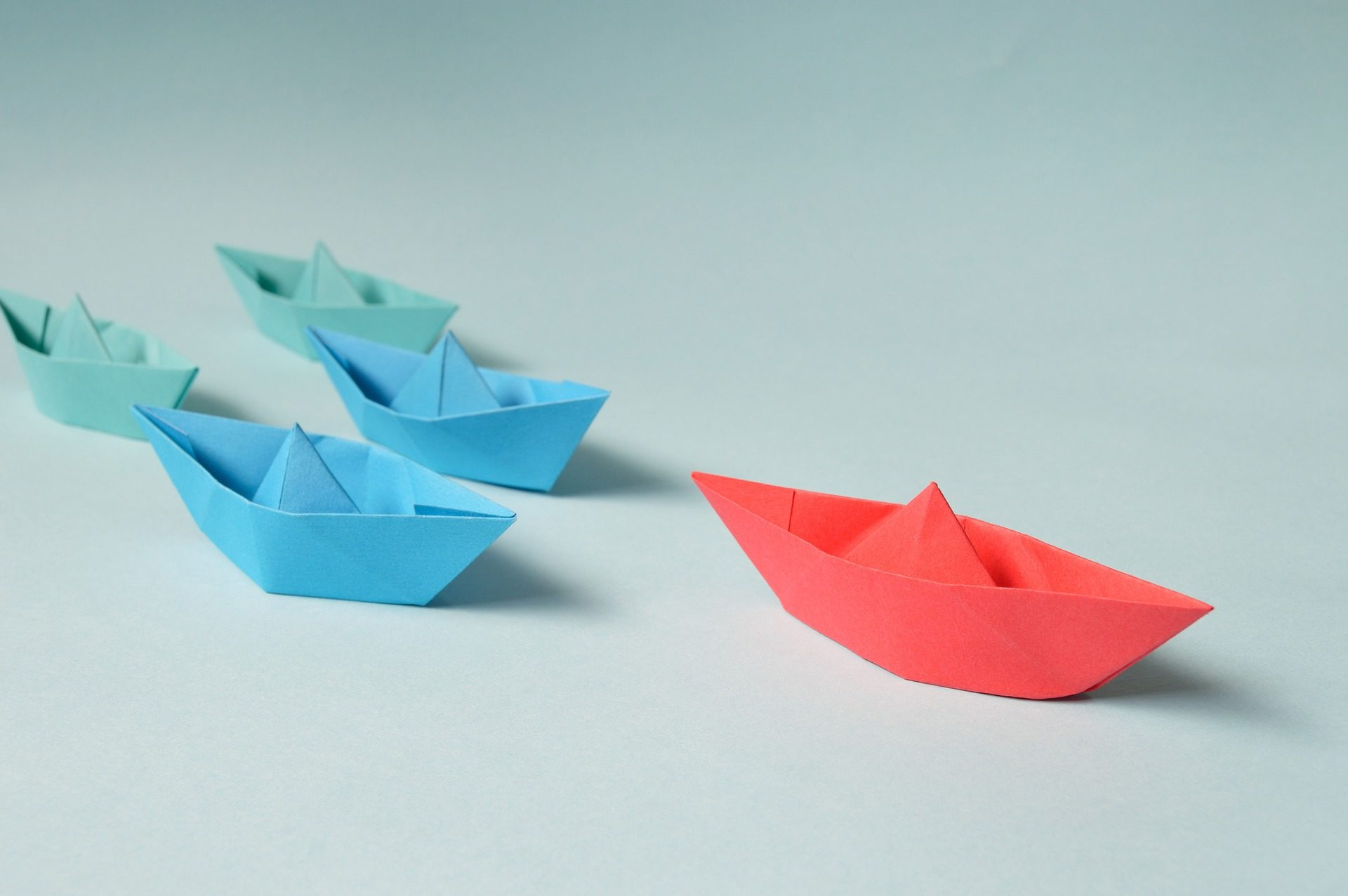 A red origami boat leads several blue boats across the photo