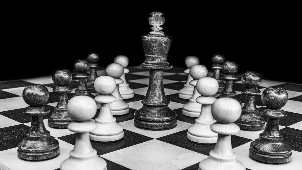 Photograph of a chess board; the King piece stands in the center of the board, while pawns from both sides surround it.