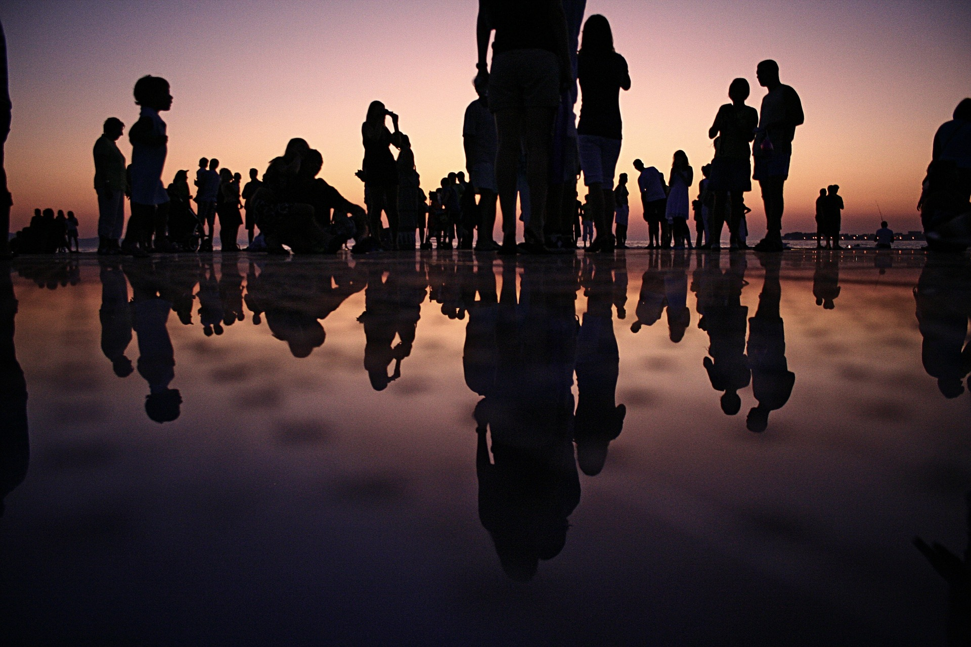 Photo of several individuals in silhouette. They are standing at the edge of a reflective surface. Some are standing, some are sitting. They range from children to adults.