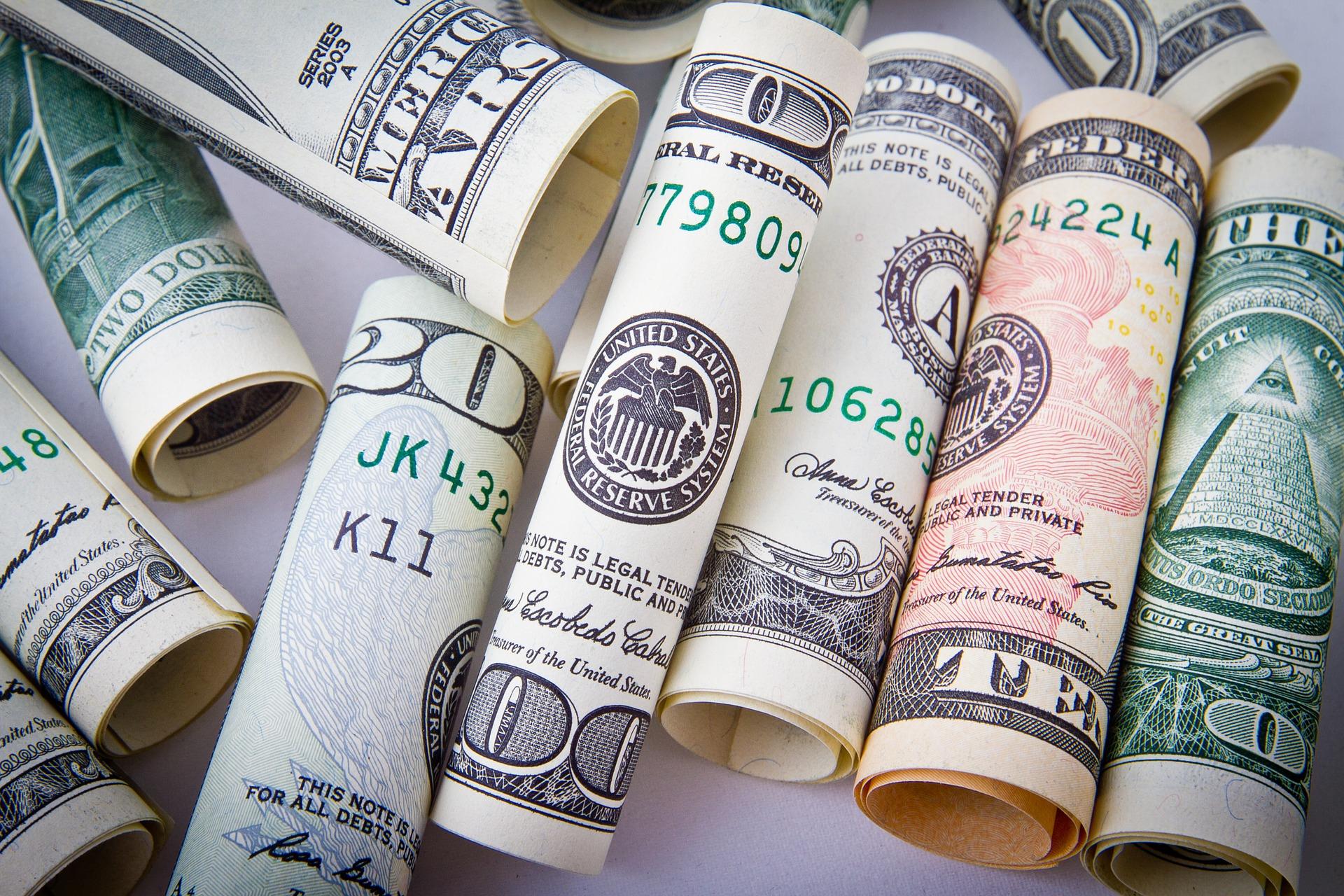 Rolls of dollar bills ranging from one dollar bills to one-hundred dollar bills.