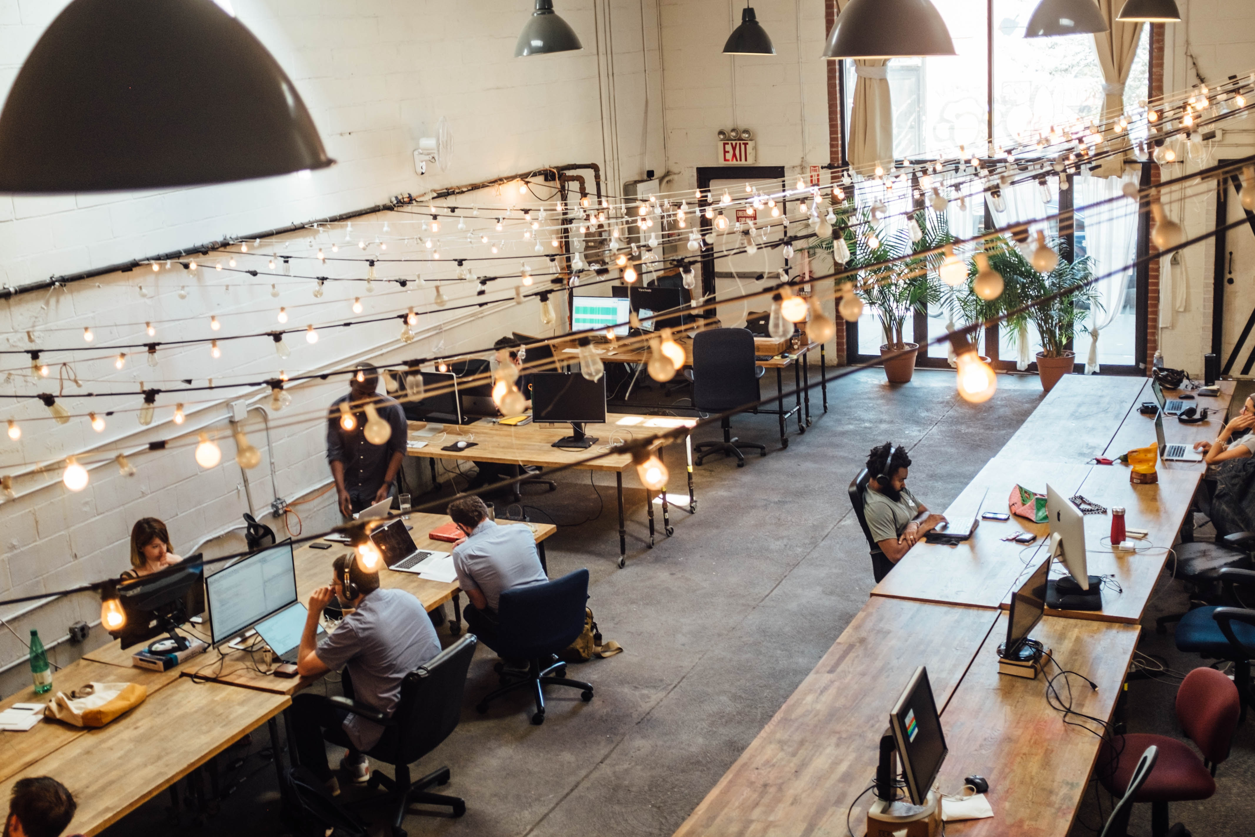 A workspace with modern wood tables. There are no walls or separation between workers. There are lights strung across the ceiling.