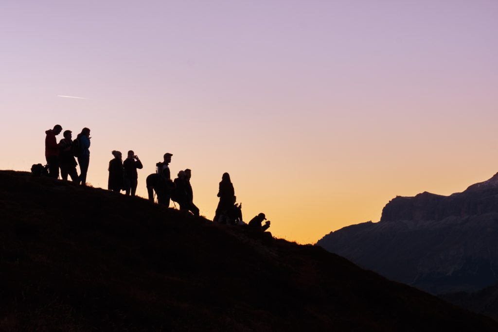 Photograph of several individuals hiking. The sun is setting, casting all individuals in shadow.