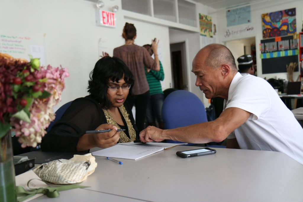 Photograph of an older man helping a young woman fill out paperwork.