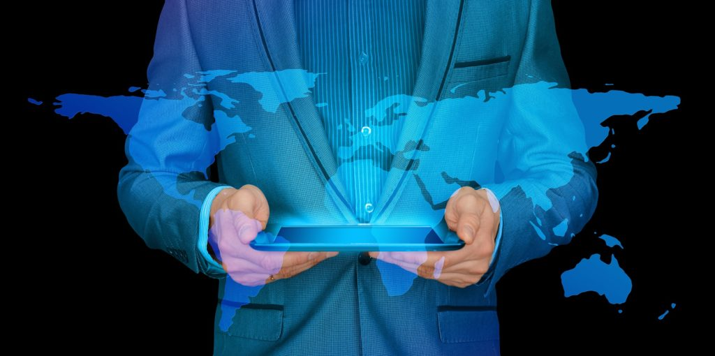 Photo of a man holding a tablet. There is a hologram image of a world map superimposed over the photo.
