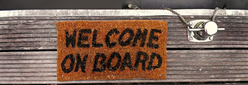 "Photograph of a welcome mat on a ship dock. The mat reads ""Welcome on board."""