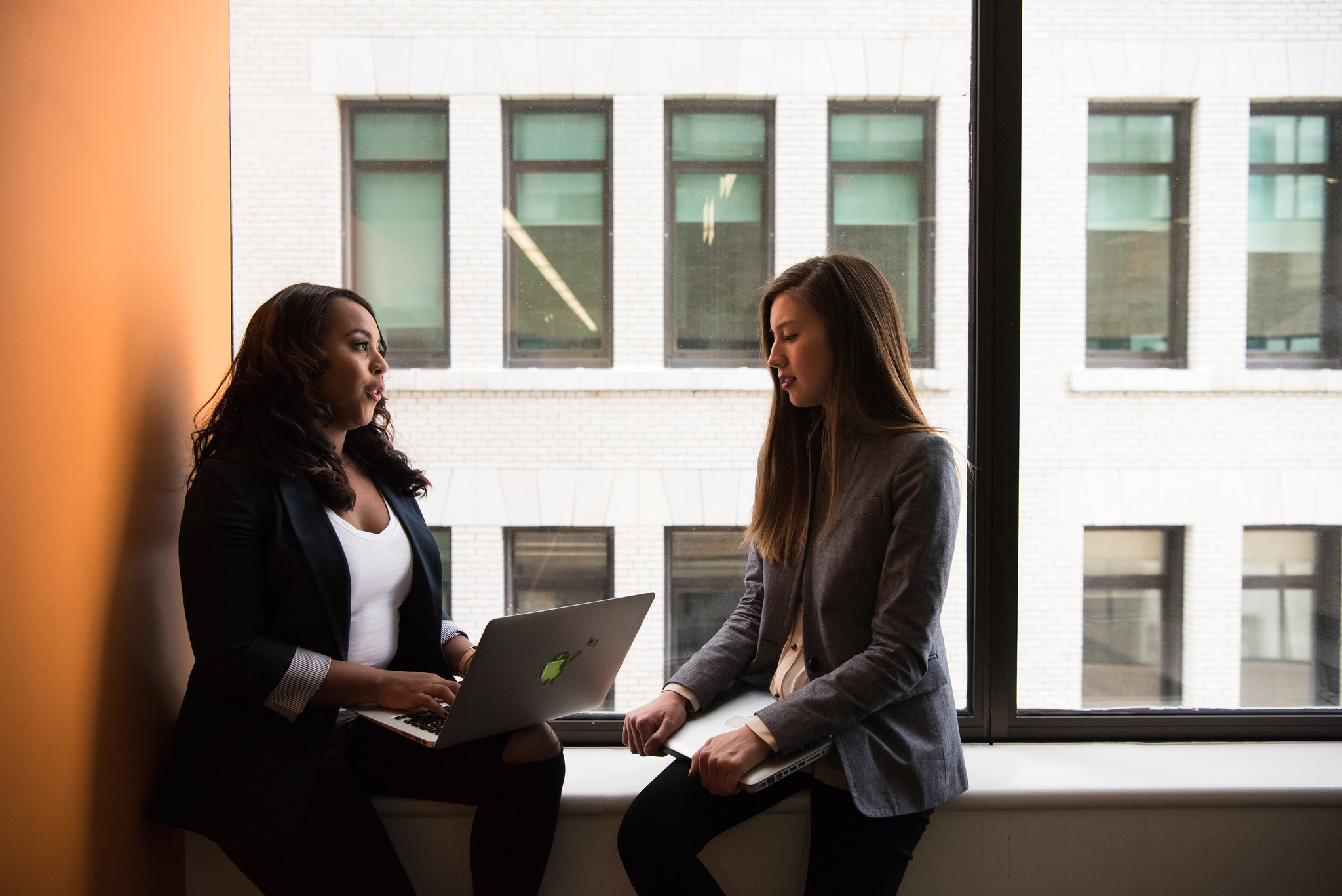 Photograph of two women sitting on a window bench. One is holding an open computer and talking to the other.