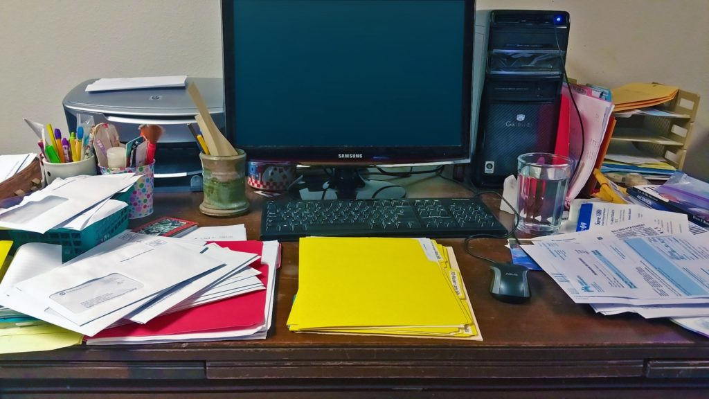A fairly cluttered desk with a computer, folders, papers, pens, and pencils
