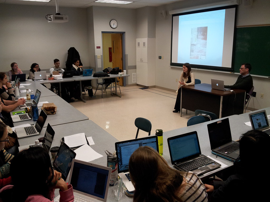 Photo of a classroom. Students are sitting at tables around the room with laptops in front of them. The teacher is at the front of the room, and an image is projected on a screen in front of the chalkboard. There are no windows, but there is a door and a clock.